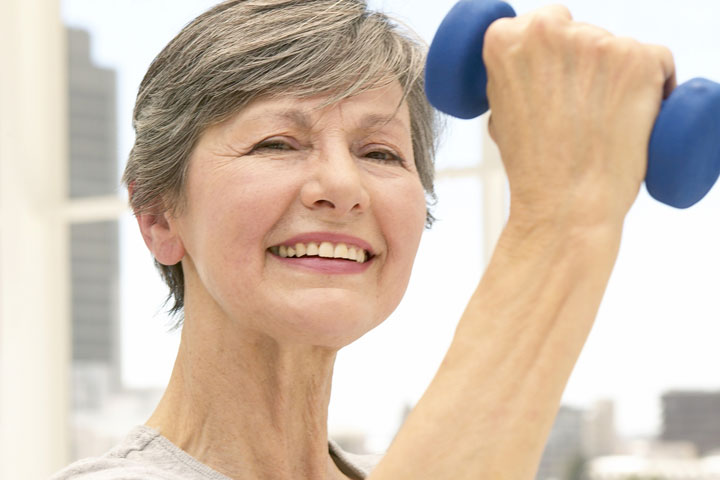 Picture of older woman exercising with smile on her face.