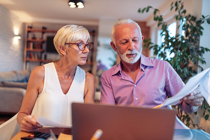 Picture of older couple reviewing bills sitting at laptop computer.