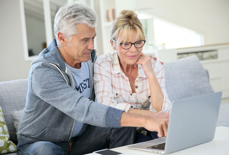 Retired couple sitting by computer shopping Medicare plans.