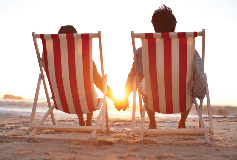 Couple sitting on beach in lounge chairs. You see them from the back with sunrise.