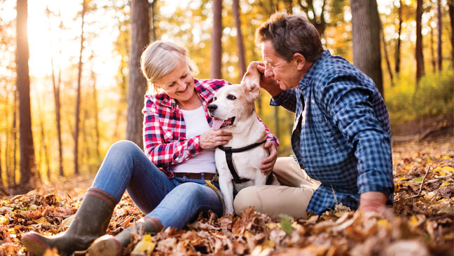 Older couple with dog sitting outside in fall leaves.